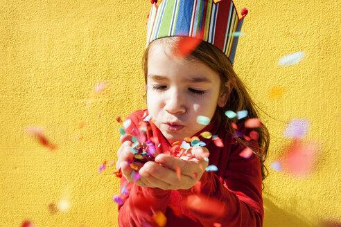 Portrait of little girl wearing paper crown blowing confetti - VABF000211