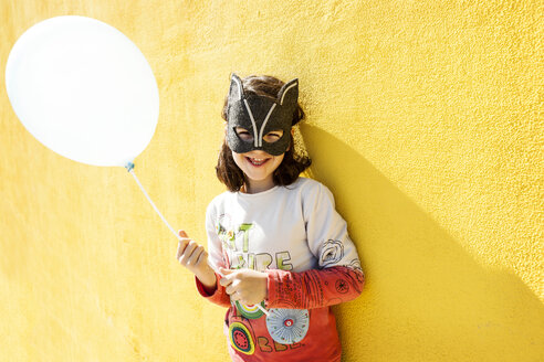 Portrait of laughing little girl with balloon wearing animal mask in front of yellow wall - VABF000214