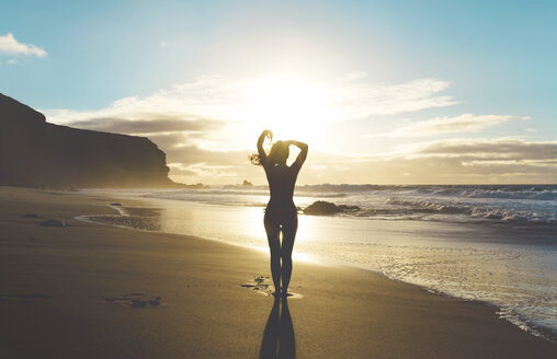 Woman standing on the beach with hands on head at sunset - GEMF000756