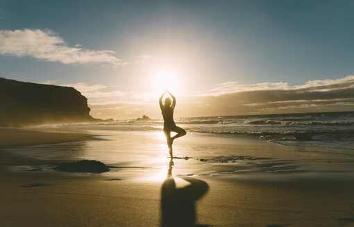 Woman practicing yoga on the beach at sunset - GEMF000759