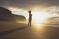 Spain, Fuerteventura, Woman standing on the beach at sunset - GEMF000762