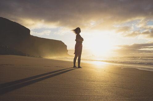 Spain, Fuerteventura, Woman standing on the beach at sunset - GEMF000762