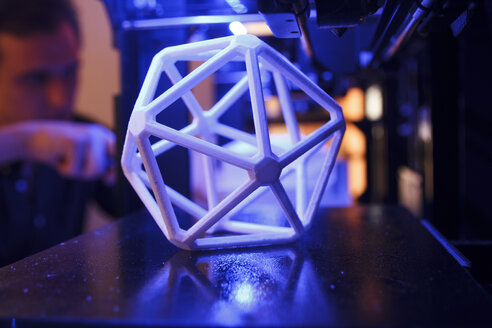 3D geometric figure on the platform of a 3D printer with a man in the background - ABZF000221