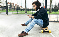 Bearded young skateboarder with smartphone and headphones - MGOF001459