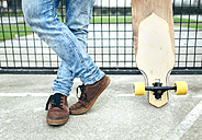 Legs of young man besides skateboard - MGOF001462