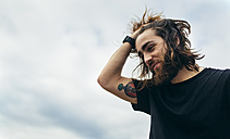 Portrait of bearded young man with tattoo on his upper arm - MGOF001471