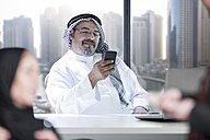Middle Eastern businessman in office using smart phone - ZEF008594