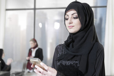 Young Middle Eastern businesswoman in office using smart phone - ZEF008597