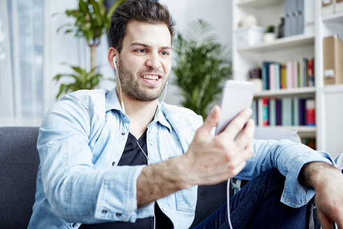 Young man at home with smartphone and earbuds - SEGF000440
