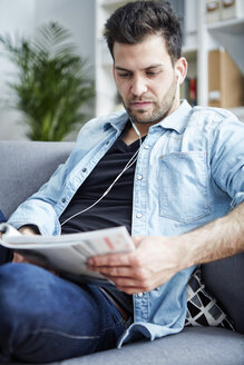 Young man at home with earbuds reading magazine - SEGF000443