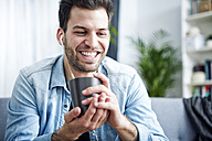 Happy young man at home with earbuds holding cup - SEGF000446