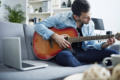 Young man at home sitting on couch playing guitar next to laptop - SEGF000452