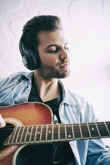 Young man wearing headphones and playing guitar - SEGF000455