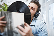 Young man wearing headphones looking at record - SEGF000461