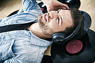 Young man wearing headphones lying on records - SEGF000464