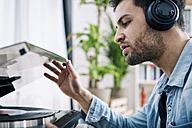 Young man wearing headphones starting record player - SEGF000467
