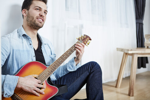 Young man sitting on floor playing guitar - SEGF000470