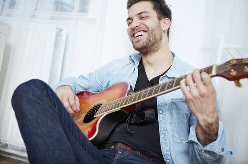 Happy young man playing guitar - SEGF000473