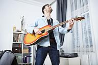 Young man at home playing guitar - SEGF000479