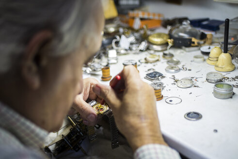 Watchmaker in foreground while working with a wristwatch - KIJF000201