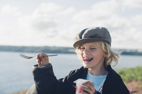 France, Brittany, Atlantic, happy boy at the coast eating yogurt - MJF001774