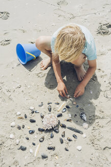 France, Brittany, Finistere, Pointe de la Torche, boy playing with seashells on the beach - MJF001786