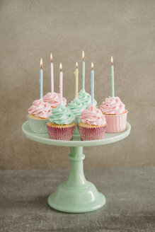 Cup cakes with lighted candles on a cake stand - ECF001855