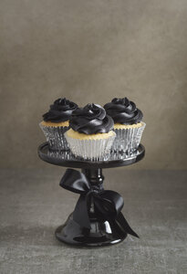 Three cup cakes with black buttercream topping on a cake stand - ECF001858