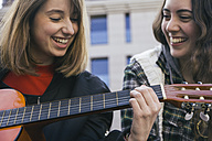 Women playing the guitar and laughing - ABZF000222