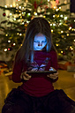 Girl looking at digital tablet at Christmas time - SARF002597