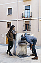 Spain, Tarragona, Young couple, man drinking from drinking fountain - JRFF000459