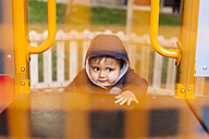 Portrait of little boy climbing on playground equipment - VABF000226