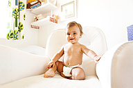 Smiling baby boy with diapers sitting on an armchair - VABF000235