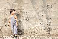 Little boy standing in front of concrete wall in summer - VABF000238