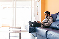 Bearded young man working at home relaxed sitting on the couch, using laptop and mobile - JRFF000471