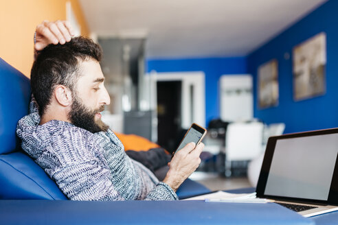 Bearded young man working at home relaxed sitting on the couch, using laptop and mobile - JRFF000474