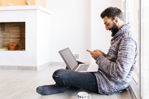 Bearded young man working at home relaxed, sitting on the floor, using laptop and mobile - JRFF000477