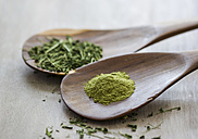 Moringa oleifera, powder and chopped leaves on wooden spoons - GSF001063
