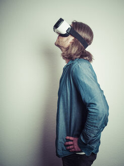 Man with hands on his hips wearing Virtual Reality Glasses looking up - KRPF001736