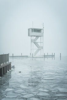Germany, Berlin-Koepenick, view to frozen Mueggelsee with diving tower in the fog - ASCF000516