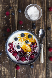 Bowl of natural yoghurt with mango pulp, grits, coconut flakes and fruits - SARF002602