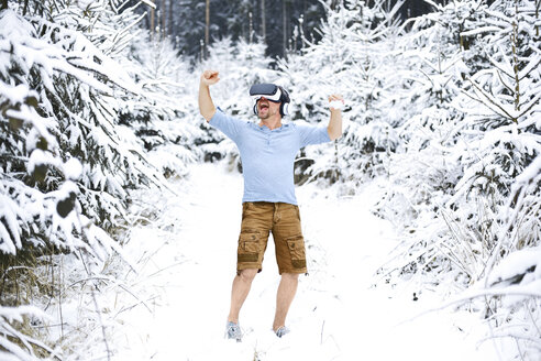 Happy man wearing Virtual Reality Glasses in winter landscape - MAEF011363