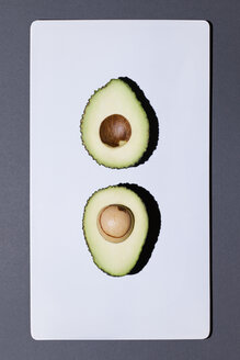 Two halves of an avocado on white board - MN000151