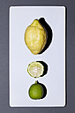 Lemon and whole and sliced lime on white board - MN000157