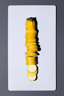 Sliced yellow zucchini on white board - MN000163
