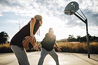 Two young men playing basketball on an outdoor court - JRFF000485