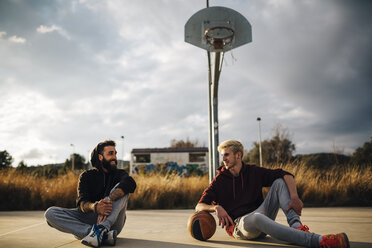 Two young men sitting on outdoor basketball court - JRFF000488