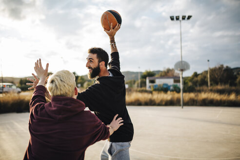 Two young men playing basketball on an outdoor court - JRFF000491
