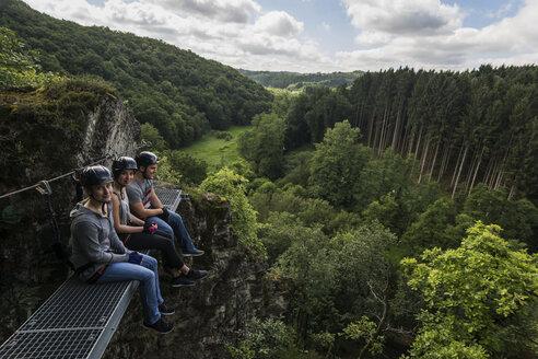 Germany, Westerwald, Hoelderstein, three friends on via ferrata having a break - PAF001553