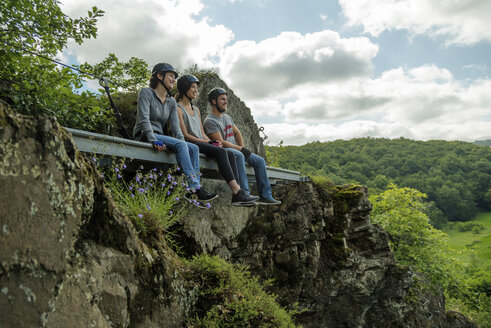 Germany, Westerwald, Hoelderstein, three friends on via ferrata having a break - PAF001556